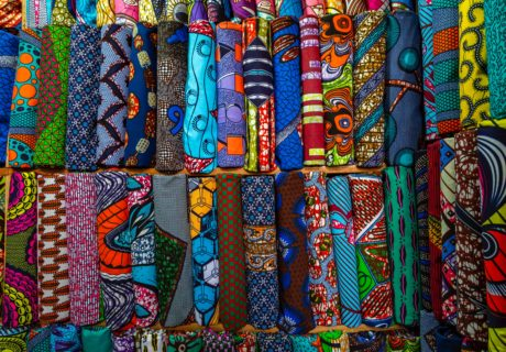 Wax print fabrics laid out to sell at a market.